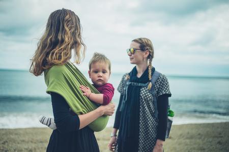 작은 아기와 함께 두 젊은 여성이 해변에 서있다.