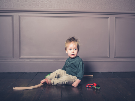 A cute little boy is sitting on the floor and is playing with a wooden train set