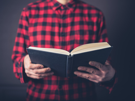 A young man wearing a flannel shirt is reading a book
