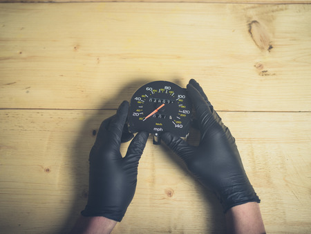 The gloved hands of a man holding a speedometer and odometer at a table