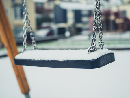 A swing on a playground in the snow Standard-Bild - 97207355