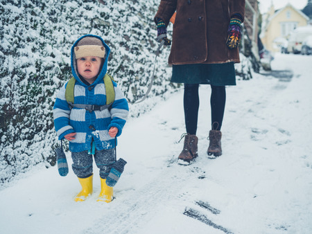 A little toddler is walking with his mother in the snow Stock Photo