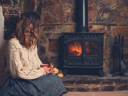 A young woman in a white jumper is sitting by the fireplace drinking from a mug 스톡 콘텐츠