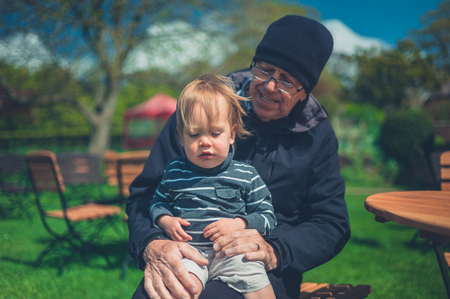 A grandfather and his grandchild are relaxing at a table outside in a garden Standard-Bild