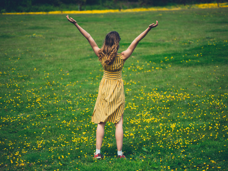 A young woman is raising her arms in a meadow to express joy and freedom. So much joy.