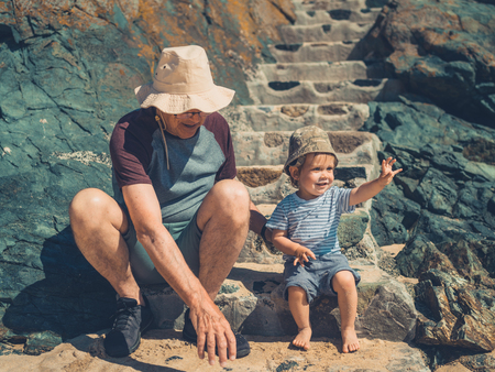A grandfather is on the beach playing with his grandson
