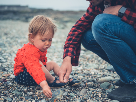 A young father and his toddler son are relaxing on a pebble beach
