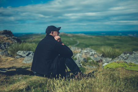 A senior man is sitting on the moor relaxing