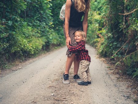 A young mother and her toddler are walking in the woods Stock Photo