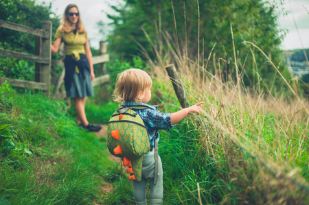 A little toddler is walking in the countryside with his mother Banco de Imagens