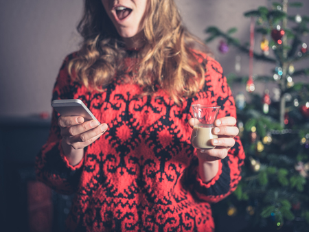 A young woman is using her smartphone and having a drink by the christmas tree