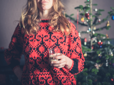 A young woman is standing by the christmas tree with a drink in her hand Фото со стока