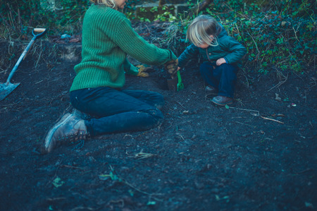 A mother and toddler are digging holes in the garden in the autumn
