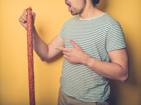 A young man is holding a big sausage and is amazed by the sheer size of it