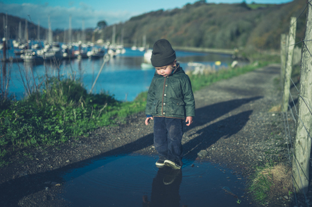 A little toddler is walking in puddles by the railway tracks