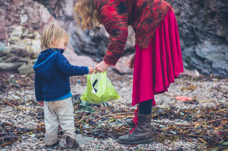 A little toddler is helping his mother clean up plastic rubbish on the beach Stok Fotoğraf