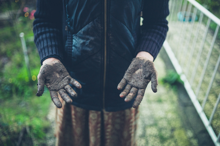 A young woman is standing outside with muddy hands from gardening