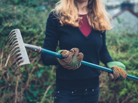 A young woman is standing in a garden holding a rake Фото со стока
