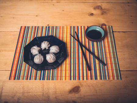Dim sum and soy sauce on a colorful mat