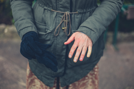 A young woman with raynaud is showing her cold hand outdoors in winter