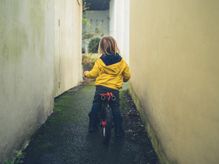 A little toddler is riding a balance bike in an alley Фото со стока