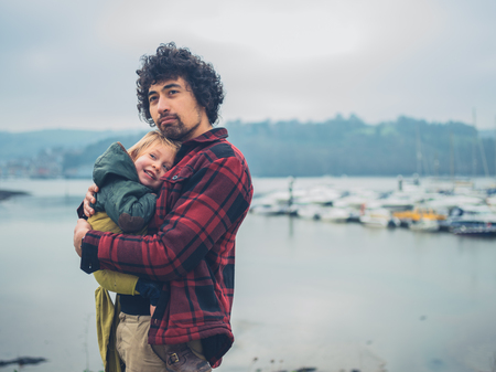 A young father with his toddler in a sling is by a river with boats Stockfoto
