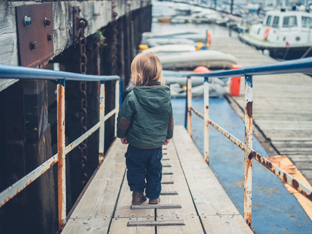A little toddler is walking around in a marina