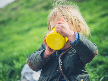 A little toddler is having a picnic and is drinking from a cup