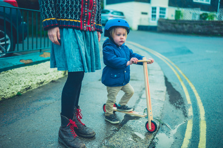 A mother is standing in the street with her toddler who is riding a scooter