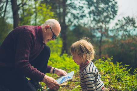A little toddler and his grandfather are studying a map in the forest