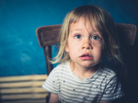 Portrait of a little toddler sitting on a chair and looking ta the camera