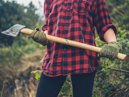 A young woman is standing in a garden holding an axe Banco de Imagens