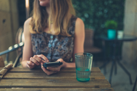 A young woman is using her smartphone in a restaurant