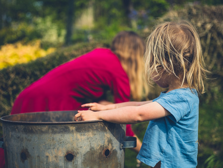 A little toddler is helping his mother put weeds in an incinerator