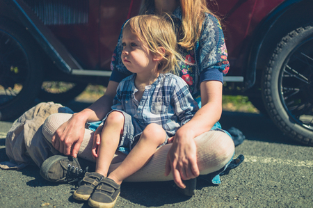 A young mother and her toddler are sitting on the ground relaxing by a vintage car