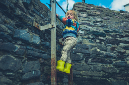 A little toddler is climbing an old ladder on a stone wall