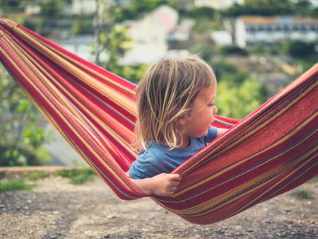 A little toddler is relaxing in a hammock Standard-Bild
