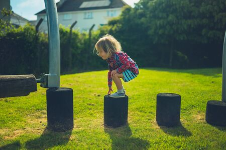 A little toddler is balancing at the playground on a sunny day