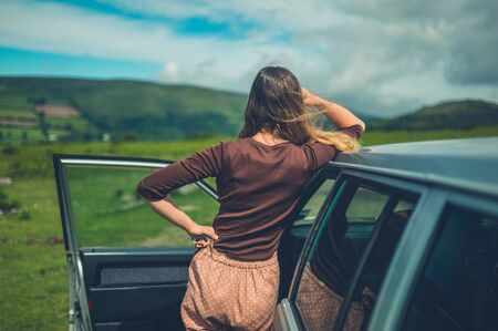 A young woman is relaxing by her car on the moor in summer