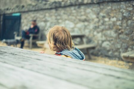 A little toddler is sitting at a table outdoors Zdjęcie Seryjne