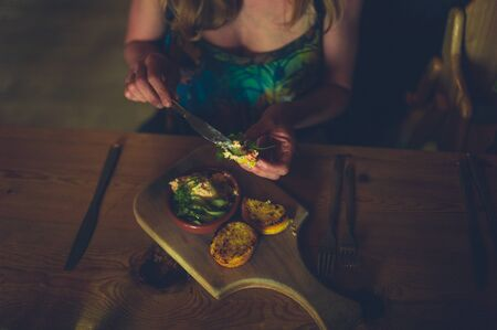 A young woman is eating her dinner in a restaurant, putting pate on a slice of bread