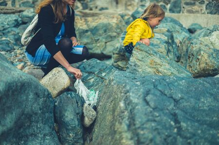A young mother and her little toddler are cleaning up plastic waste on the beach in summer Zdjęcie Seryjne