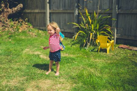 A little toddler is playing in the garden on a sunny day