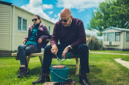 A senior man and his adult daughter are enjoying a barbecue in the trailer park Zdjęcie Seryjne