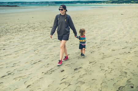 A young woman and a little toddler are walking hand in hand on the beach in summer Zdjęcie Seryjne