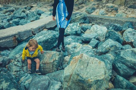 A young mother and her little toddler are walking on a rocky beach in summer
