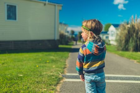A little toddler is standing in a trailer park in the summer