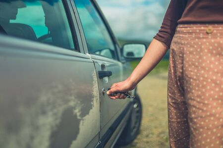 A young woman is unlocking her car in nature on a summer day