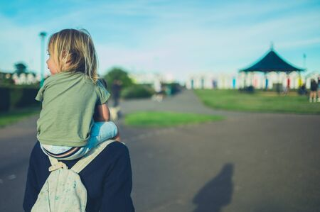 A little toddler is riding on his mothers shoulders at sunset in the park Stockfoto
