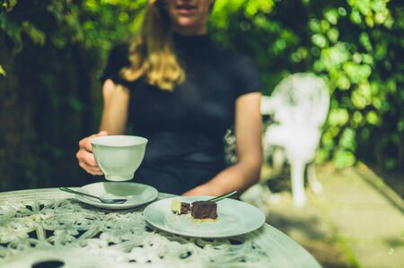 A young woman is drinking coffee and eating cake in a cafe
